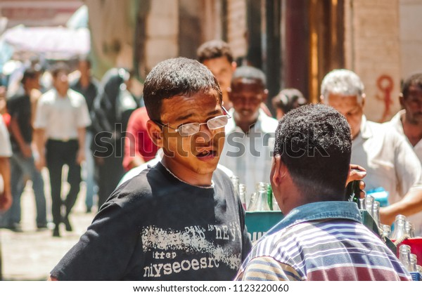 Cairo, Egypt - 2008 - An old image for a teenager working as a delivery boy, walking and pushing soda drink boxes in Muizz Street in Cairo, Egypt.