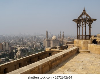 Cairo, Egypt, 22th of February 2020: a look over cairo skyline with its mosques and towers and the smog and a man sitting and thinking in the foreground