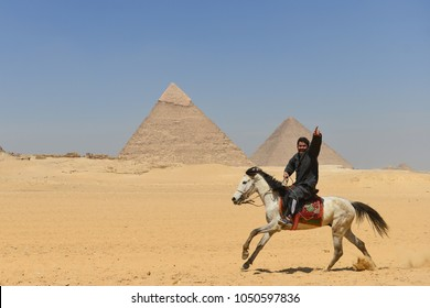 Cairo / Egypt - April 03 2016: A horseman riding with a great joy in Giza Pyramids area. Horseback and camel riding  are traditional rituals at the grounds of Giza Pyramids.