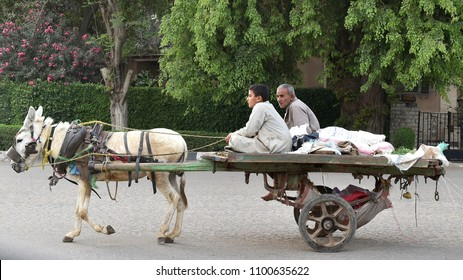 Cairo, Egypt - April 20, 2018: Market traders ride a donkey pulled cart on a city street.