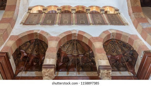 Cairo, Egypt - August 11 2018: Three arches revealing three wooden domes decorated with floral patterns with interleaved wood window (Mashrabiya) located at the Mamluk era Beshtak Palace