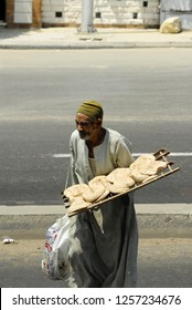 CAIRO, EGYPT - AUGUST 3: The poor old man sells wheat flat cakes near a road on August 3, 2006 in Cairo.