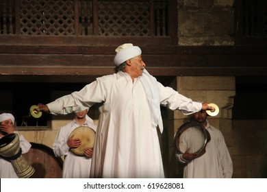 CAIRO, EGYPT - CIRCA APRIL 2017: An old and fun Egyptian dervish dressed in white performs at a traditional tanoura concert accompanied by young dervishes.