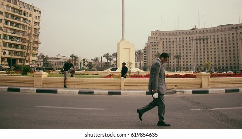 CAIRO, EGYPT - CIRCA APRIL 2017: A classy Egyptian man wearing a grey suit walks around post-revolution Tahrir Square in Downtown Cairo.
