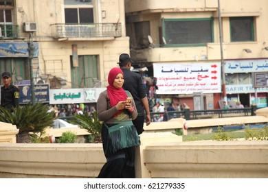 CAIRO, EGYPT - CIRCA APRIL 2017: A veiled Egyptian woman is texting on her phone while crossing Tahrir Square.