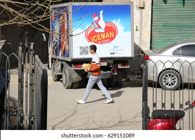 CAIRO, EGYPT - CIRCA APRIL 2017: A young Egyptian man passes in front of an ice cream truck with fresh bread in his hands on the streets of Islamic Cairo.