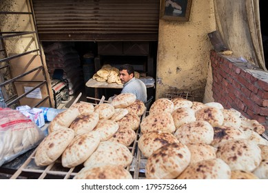 Cairo / Egypt - December 12, 2019: baker in shop selling traditional puffed and round bread on street of Cairo