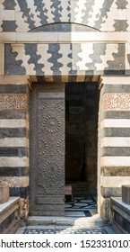 Cairo, Egypt- December 19 2015: Old grunge decorated bronze-plate door surrounded by striped black and white marble decorations and stone wall at public historic mosque of Sultan Barquq, Moez Street