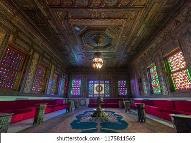 Cairo, Egypt - December 2 2017: Manial Palace of Prince Mohammed Ali. Syrian Hall with ornate wooden wall and ceiling, windows with colored stained glass, ornate chandelier and red couches