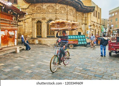 CAIRO, EGYPT - DECEMBER 21, 2017: Traditional bread delivery in old town, cyclist with large wooden basket rides next to  Sabil wa Kuttab of Tusun Pasha in Al-Muizz street, on December 21 in Cairo.