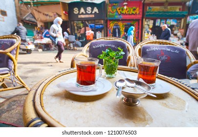 CAIRO, EGYPT - DECEMBER 21, 2017: Enjoy a glass of hot black tea, serving with fresh mint in outdoor teahouse, located in Al Khayama street, occupied with shops and stalls, on December 21 in Cairo.