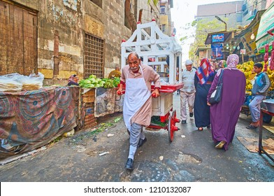 CAIRO, EGYPT - DECEMBER 21, 2017: The street food seller walks along Al Khayama street with his food cart, on December 21 in Cairo.
