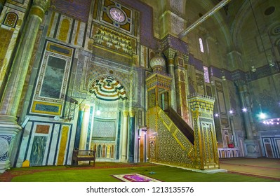 CAIRO, EGYPT - DECEMBER 21, 2017: The complex wooden minbar of Al-Rifai (Royal) Mosque with fine carvings and ivory inlay stands next to the stone mihrab with mosaic ornaments, on December 21 in Cairo