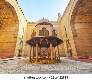 CAIRO, EGYPT - DECEMBER 21, 2017: The courtyard of Sultan Hassan Mosque-Madrasa with ornamented stone tiles on the floor and carved ablution fountain amid deep arched niches, on December 21 in Cairo