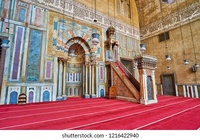 CAIRO, EGYPT - DECEMBER 21, 2017: The complex stone decoration of mihrab in Sultan Hassan Mosque with carvings, inlay, gilt insciptions and slender pillars around the niche, on December 21 in Cairo