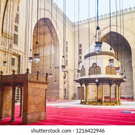 CAIRO, EGYPT - DECEMBER 21, 2017: The courtyard of Sultan Hassan Mosque-Madrasa with beautiful ablution fountain through the numerous oil lamps, hanging on the long chains, on December 21 in Cairo