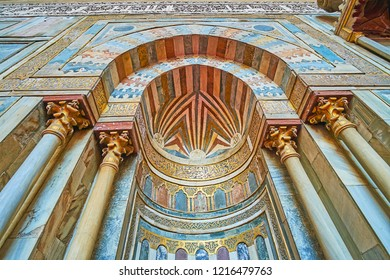 CAIRO, EGYPT - DECEMBER 21, 2017: The close-up of medieval mihrab of Sultan Hassan Mosque, decorated with pillars, golden Arabic calligraphy and fine patterns of stone tiles, on December 21 in Cairo.