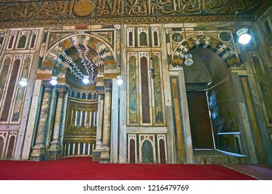 CAIRO, EGYPT - DECEMBER 21, 2017: Mihrab of Sultan Hassan Mosque-Madrasa is decorated with gilt Arabic inscriptions, stone pillars and geometric patterns of colored stone tile, on December 21 in Cairo