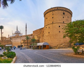CAIRO, EGYPT - DECEMBER 21, 2017: The tall stone wall of Saladin Citadel with old watchtowers and rising minarets of Alabaster Mosque, on December 21 in Cairo