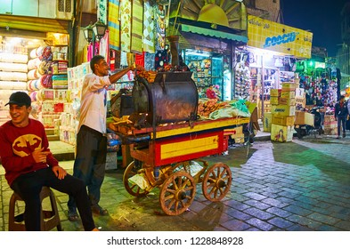 CAIRO, EGYPT - DECEMBER 21, 2017: The street seller of sweet potato cooks batata in oven, standing on his food cart in Al Muizz street of old Bazaar, on December 21 in Cairo.