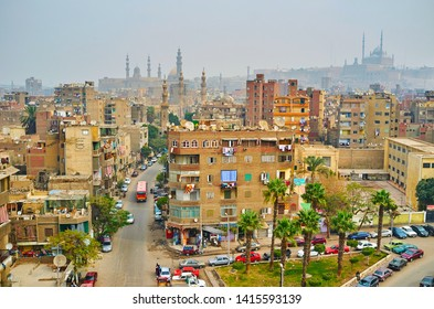 CAIRO, EGYPT - DECEMBER 22, 2017: Tall minaret of Amir Sarghatmish madrasa opens view on shabby Al Khoderi street with poor housing and Saladin Citadel on background, on December 22 in Cairo, Egypt.