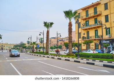 CAIRO, EGYPT - DECEMBER 22, 2017: Walk El Tahrir avenue with a view on slender palm trees, stores, residential housing and Abdeen palace in El-Gomhoreya Square on background, on December 22 in Cairo.