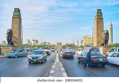 CAIRO, EGYPT - DECEMBER 24, 2017: The fast traffic on El Tahrir road, leading to the Qasr El Nil bridge, guarding with lions' sculprtures, on December 24 in Cairo.