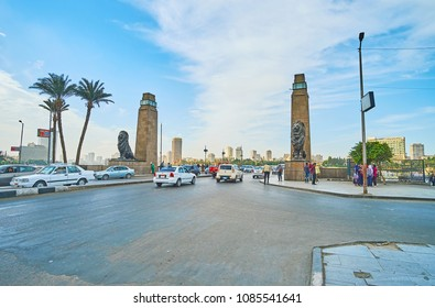 CAIRO, EGYPT - DECEMBER 24, 2017: The busy El Tahrir road, decorated with stone towers and sculprtures of lions at the entrance of Qasr El Nil bridge, on December 24 in Cairo.