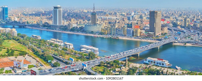 CAIRO, EGYPT - DECEMBER 24, 2017: The high-rises of Downtown district on the bank of Nile river with a view on 6th of October bridge, full of cars, on December 24 in Cairo