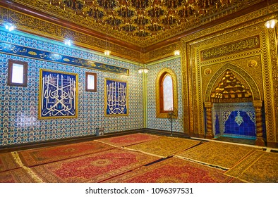 CAIRO, EGYPT - DECEMBER 24, 2017: The prayer hall of Manial Palace mosque with ornate patterns on tiled walls, complex wooden Rococo ceiling and beautiful golden mihrab, on December 24 in Cairo