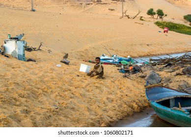 Cairo, Egypt February 18, 2017: Small ethnic Nubian boy sitting playing with the sand on the bank of the Nile River very close to Cairo. The shore is full of garbage and with boats docked