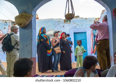 Cairo, Egypt February 18, 2017: Young woman is photographed among two other ethnic Nubian women in the courtyard of a typical house blue-washed while a Nubian girl looks at them surprised