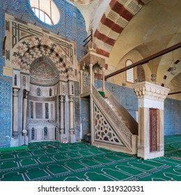Cairo, Egypt - January 8 2019: Blue, Iznik ceramic tiles wall with engraved Mihrab (niche) and decorated marble Minbar (Platform) at the Mosque of Aqsunqur (Blue Mosque)
