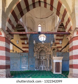 Cairo, Egypt - January 8 2019: Blue, Iznik ceramic tiles wall with engraved Mihrab (niche) and decorated marble Minbar (Platform) framed by stone arch at the Mosque of Aqsunqur (Blue Mosque)