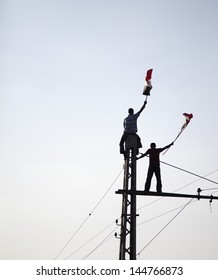 """CAIRO, EGYPT - JULY 1: Two young Egyptians protesting on top of tramway pole holding Egyptian flag near El-Etehadeya palace during """"June 30"""" protests against Mohamed Morsy. CAIRO - July 1, 2013"""