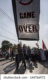"""CAIRO, EGYPT - JULY 1:Egyptian protesting carrying big flag with """"Game Over"""" written on it, in El-Etehadeya district during """"June 30"""" protests against Mohamed Morsy. CAIRO - July 1, 2013"""