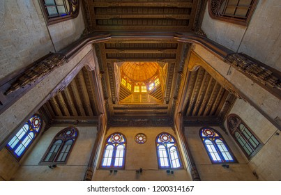 Cairo, Egypt - July 28 2018: Wooden decorated dome mediating ornate ceiling with floral pattern decorations and stained glass windows at Sultan al Ghuri Mausoleum