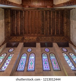 Cairo, Egypt - July 28 2018: Wooden ornate ceiling with floral pattern decorations and colorful stained glass windows at Sultan al Ghuri Mausoleum