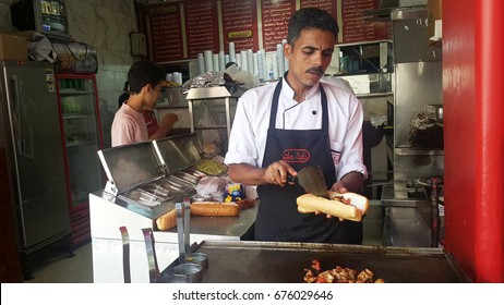 CAIRO, EGYPT- JULY 8TH, 2017.  A restaurant worker preparing chicken sandwiches at one of the restaurant in Cairo