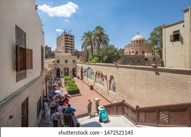 CAIRO, EGYPT - JUNE 10, 2019:  Stairs of Hanging Church (Saint Virgin Mary's Coptic Orthodox Church) with group of tourists and Church of St. George in background