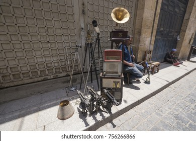 Cairo, Egypt, June 2013: A man smokes from a water pipe or shisha on a street of old Cairo seating next to few old artifacts he is selling.