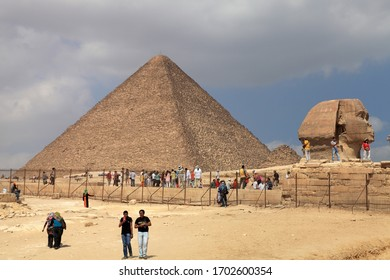 Cairo / Egypt - March 16, 2010: A pyramid and great sphinx in the Giza district of Cairo. Tourists located in front of the pyramid. Pyramids are on the Unesco world heritage list.