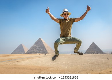 Cairo, Egypt - Nov 4th 2018 - A young man tourists having fun taking a picture in front of the pyramids of Giza in Cairo, capital of Egypt