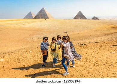 Cairo, Egypt - Nov 4th 2018 - Chinese tourists having fun taking a selfie picture in front of the pyramids of Giza in Cairo, capital of Egypt