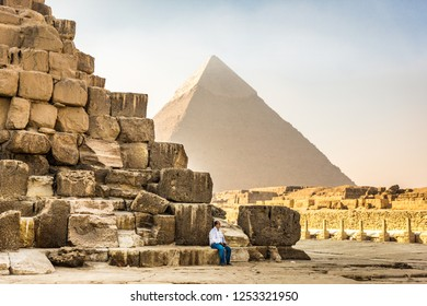 Cairo, Egypt - Nov 4th 2018 - A person sitting at the pyramid of Khafre with the pyramid of Khufu in the Giza Complex at the Cairo city in a haze, fog day in Egypt