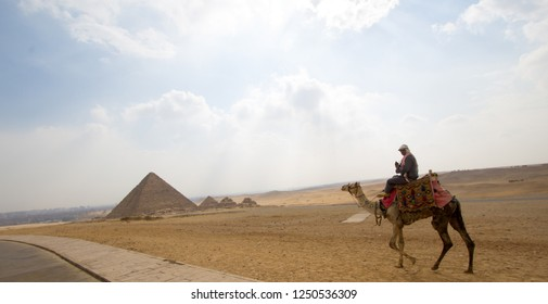 Cairo, Egypt – November 12, 2018: photo for Pyramid of Khufu in the Pyramids of Giza in Cairo city capital of Egypt. and Pyramid of Khafra And a man riding camel