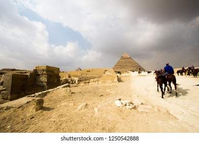 Cairo, Egypt – November 12, 2018: photo for Pyramid of Khufu in the Pyramids of Giza in Cairo city capital of Egypt. and Pyramid of Khafra And a man riding hourse