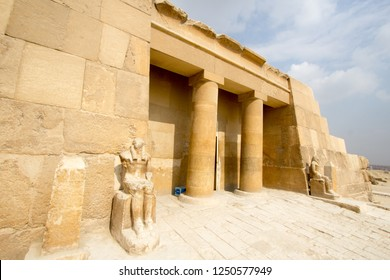 Cairo, Egypt – November 12, 2018: photo for Pharaonic Cemetery in the Pyramids of Giza in Cairo city capital of Egypt.and showing two poles and Two Pharaonic Statues.