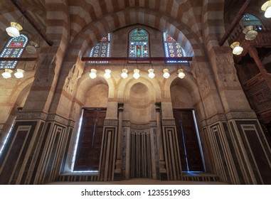 Cairo, Egypt - November 3 2018: Marble wall with mihrab (Embedded niche), wooden doors, huge arches and stained glass windows at Khayer Bek Mausoleum, Darb Al-Ahmar district, Old Cairo, Egypt