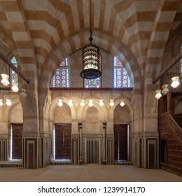 Cairo, Egypt - November 3 2018: Marble wall with mihrab (Embedded niche), two wooden doors, huge arches, stained glass windows and chandelier at mosque attached to Khayer Bek Mausoleum